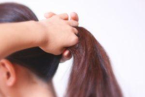 ポニーテールに髪を結ぶ女性